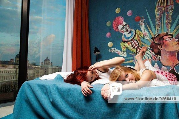 Two sleepy young women lying on hotel bed
