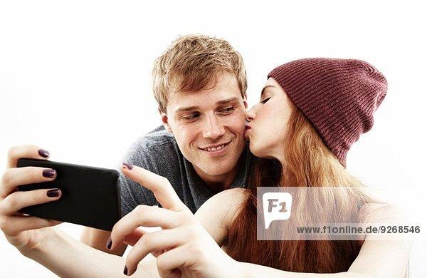 Studio-Porträt eines jungen Paares  das Selfie auf dem Smartphone nimmt.