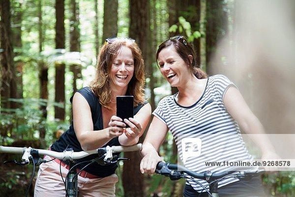 Zwei Mountainbikerinnen beim Blick auf das Smartphone im Wald