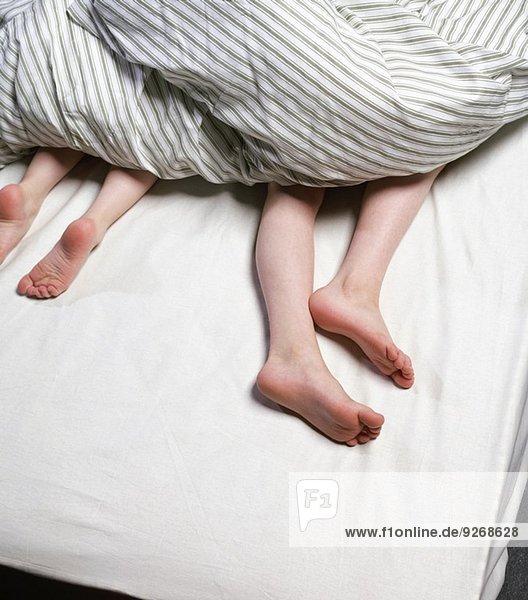 Knabenbeine unter der Bettdecke