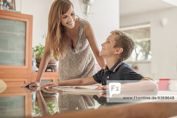 Mother and son doing homework at dining room table