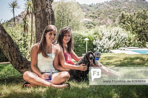 Portrait von zwei Freundinnen mit Hund im Ferienhausgarten  Capoterra  Sardinien  Italien