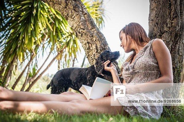 Mittlere erwachsene Frau Streichelhund im Ferienhausgarten  Capoterra  Sardinien  Italien