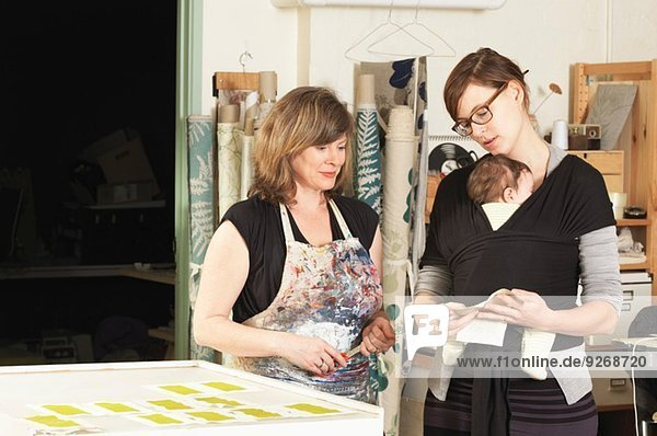 Women discussing design in hand-printing textile workshop