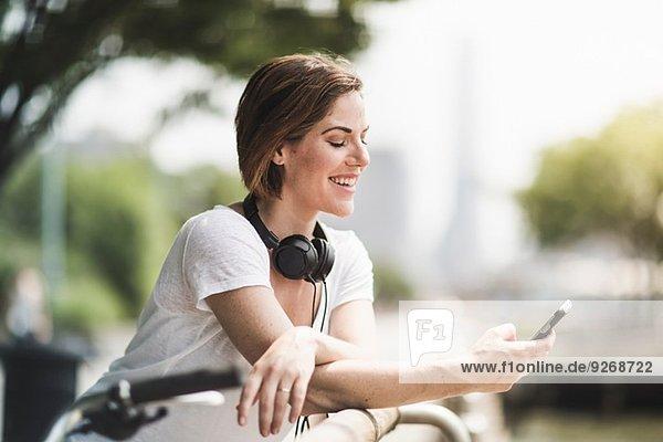 Mittlere erwachsene Radfahrerin beim Betrachten von Texten auf ihrem Smartphone