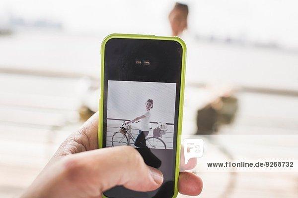 Männliche Hand fotografiert Freundin und Fahrrad mit Smartphone am Flussufer  New York City  USA