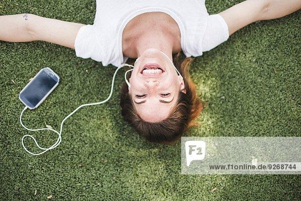 Overhead-Porträt einer erwachsenen Frau  die im Park Kopfhörer hört.