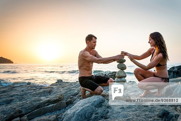 Couple on beach building tower from rocks