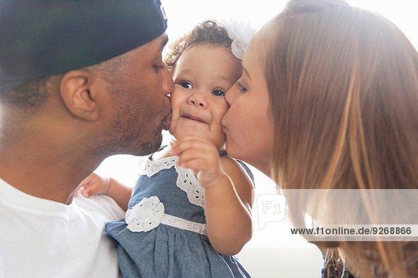 Mutter und Vater küssen die kleine Tochter auf die Wangen.
