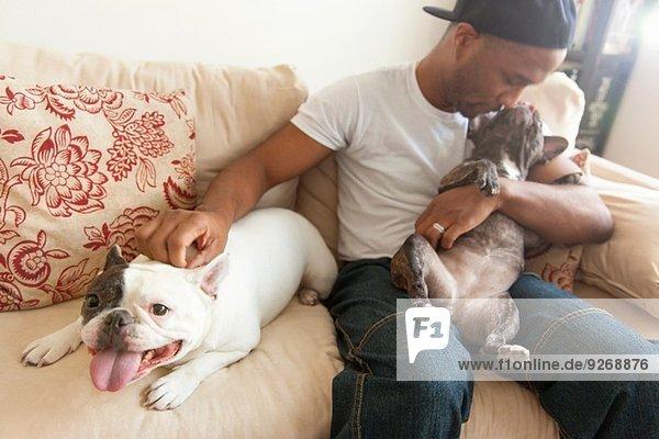 Mittlerer Erwachsener Mann sitzend mit zwei französischen Bulldoggen