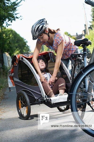 Mutter befestigt den Sicherheitsgurt der Tochter im Fahrradanhänger
