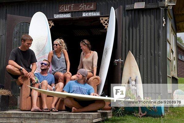 Fünf junge erwachsene Surferfreunde beim Plaudern vor dem Schuppen