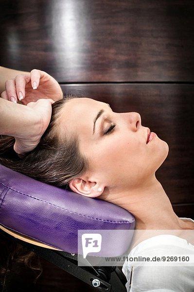 Masseurin  die den Kopf einer jungen Frau im Schönheitssalon massiert.