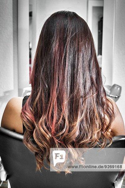 Rückansicht der jungen Frau im Friseursalon mit langen brünetten Haaren mit Wellen und rosa Highlights