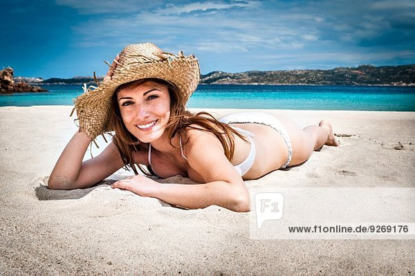 Portrait einer jungen Frau mit Bikini und Sonnenhut am Strand  La Maddalena  Sardinien  Italien