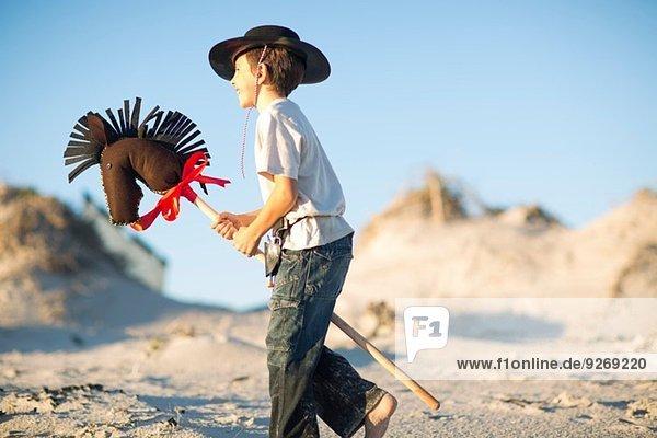 Junge mit Hobbypferd als Cowboy in Sanddünen verkleidet
