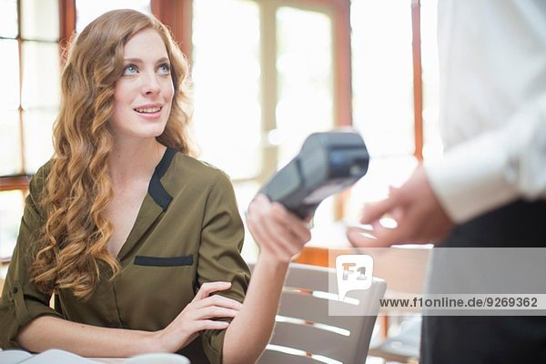 Young woman handing card machine reader to waiter in restaurant