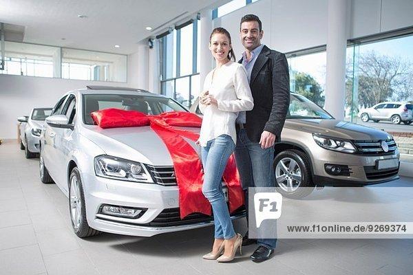 Porträt des mittleren Erwachsenenpaares und Neuwagen mit roter Schleife im Autohaus