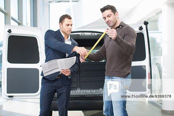 Kunde und Verkäufer bei der Prüfung von Lieferwagenabmessungen im Autohaus