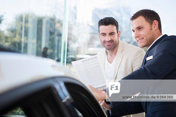 Männlicher Kunde und Verkäufer im Autohaus im Gespräch