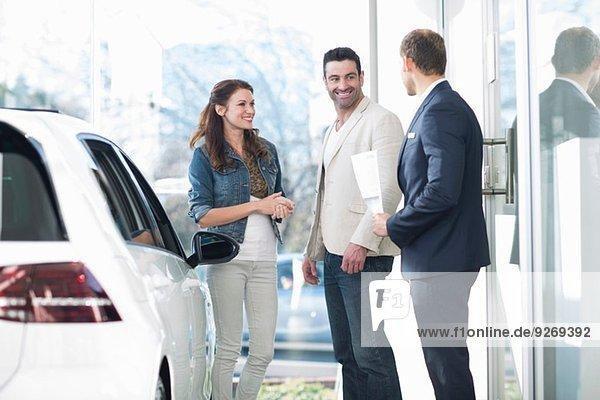 Verkäufer und mittleres erwachsenes Paar beim Plaudern im Autohaus