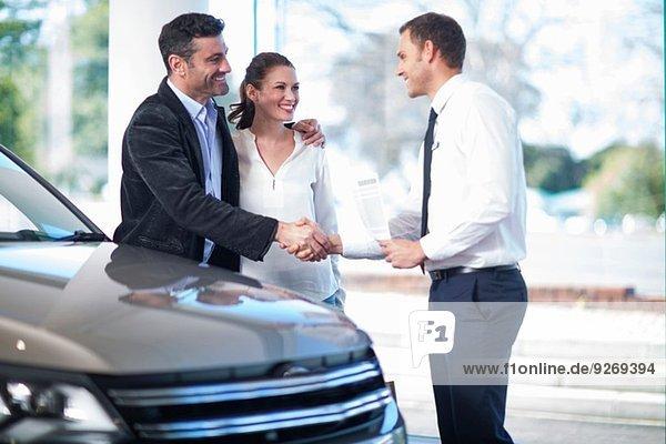 Mittleres erwachsenes Paar schüttelt sich die Hand mit dem Verkäufer im Autohaus.