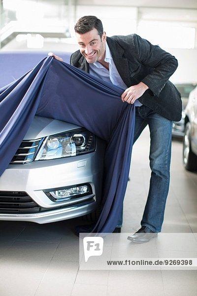 Mittlerer Erwachsener Mann entdeckt neues Auto im Autohaus