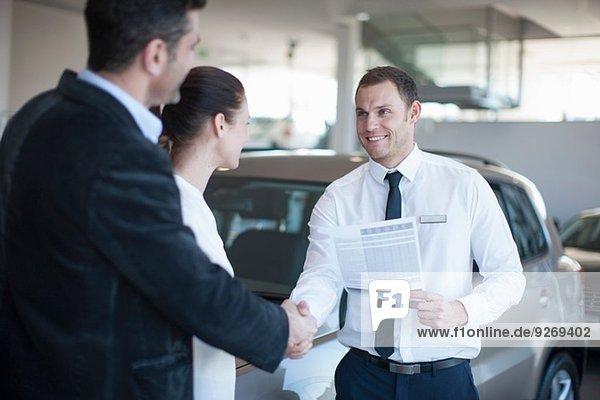 Mittleres erwachsenes Paar  das einen Deal mit einem Verkäufer im Autohaus macht.