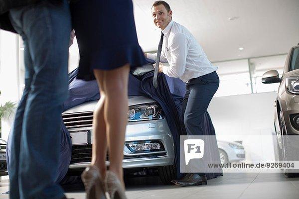 Niederwinkelansicht des Verkäufers  der ein neues Auto für ein mittelgroßes Paar im Autohaus aufdeckt.