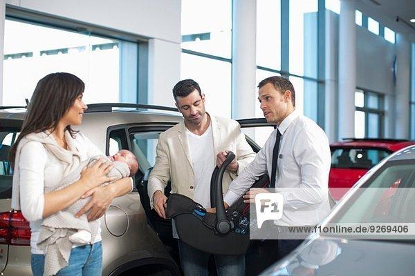 Verkäufer im Gespräch mit dem mittleren erwachsenen Paar mit dem kleinen Mädchen im Autohaus