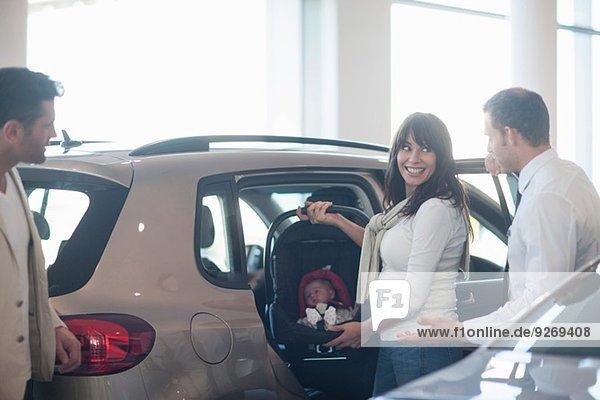 Mittleres erwachsenes Paar mit Baby Girl beim Ausprobieren des Kindersitzes im Autohaus