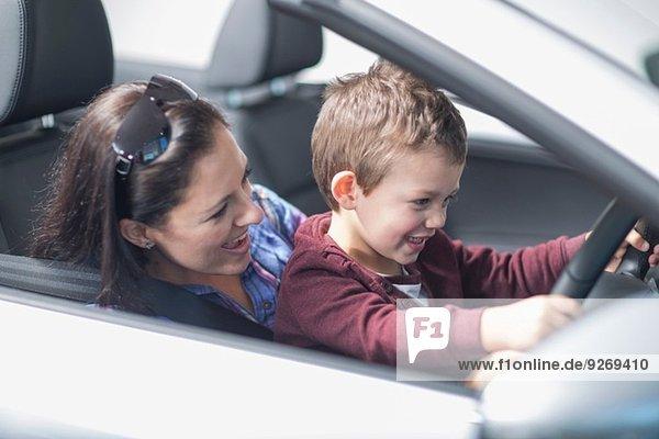 Mutter und Sohn beim Ausprobieren eines neuen Autos im Autohaus