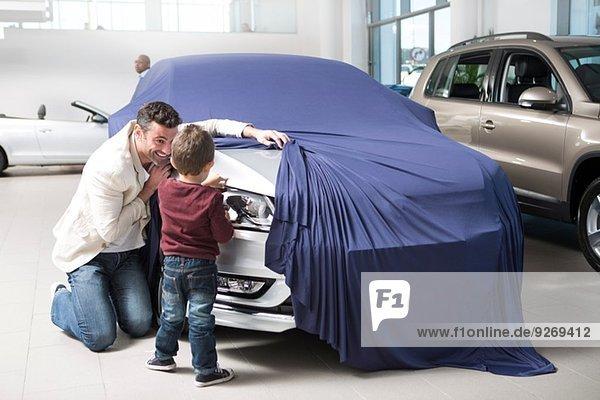 Mittlerer Erwachsener Mann entdeckt neues Auto für Sohn im Autohaus