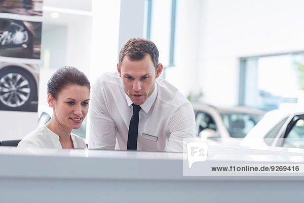 Verkäufer und Verkäuferin am Schreibtisch im Autohaus