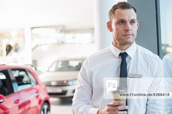 Porträt eines besorgten Verkäufers mit Kaffee zum Mitnehmen im Autohaus