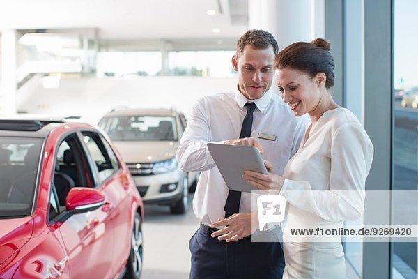 Verkäufer und Kundin mit digitalem Tablett im Autohaus