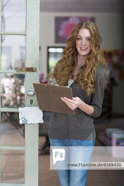 Portrait of young female gift shop assistant with clipboard