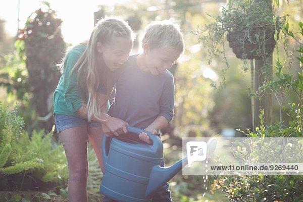 Bruder und Schwester bewässern Pflanzen auf Zuteilung