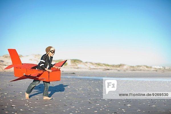 Junge rennt mit Spielzeugflugzeug am Strand Junge rennt mit Spielzeugflugzeug am Strand