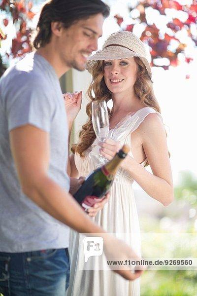 Paar bereitet sich auf die Feier mit Champagner in der Garten-Weinstube vor