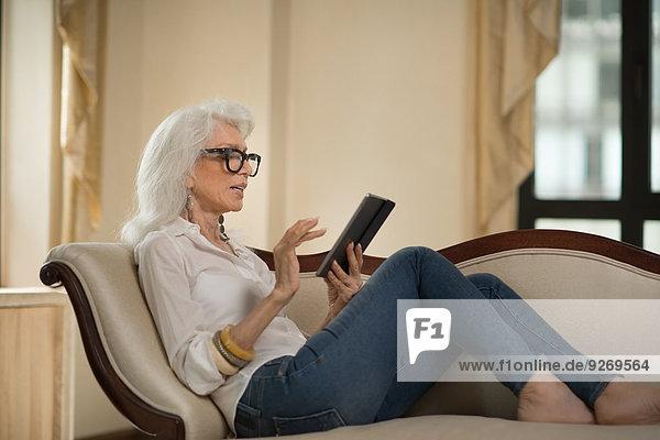 liegend liegen liegt liegendes liegender liegende daliegen Senior Senioren benutzen Frau Couch Tablet PC zurücklehnen
