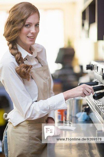Portrait of waitress using coffee machine in restaurant