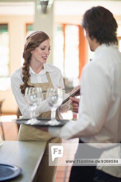 Kellnerin und Kellnerin mit Tabletts mit Weingläsern im Restaurant