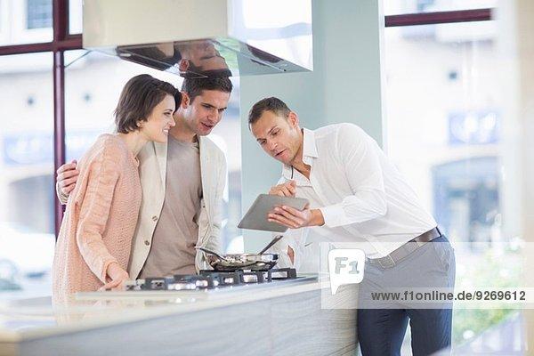 Mittleres erwachsenes Pärchen und Verkäufer beim Betrachten des digitalen Tabletts im Küchen-Showroom