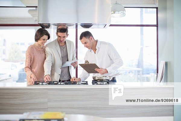Mittleres erwachsenes Pärchen und Verkäufer beim Blick auf das Kochfeld im Küchen-Showroom