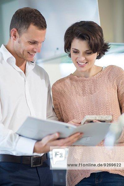 Salesman and female customer looking at brochure in kitchen showroom