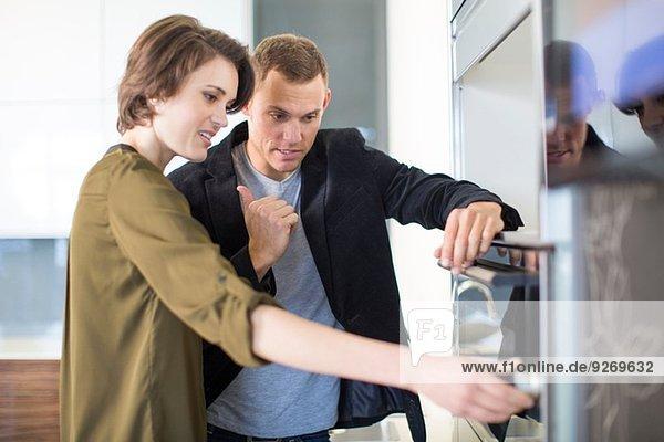 Mittleres erwachsenes Paar  das den Ofen im Ausstellungsraum der Küche inspiziert.