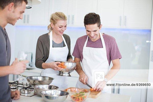 Ein erwachsener Mann hackt Karotten  während Freunde in der Küche zuschauen.
