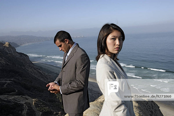 View of a man and a woman standing on a cliff.