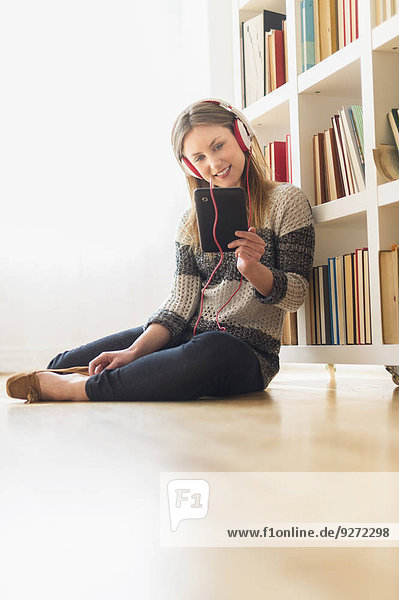 Young woman sitting on floor and listening to music on digital tablet